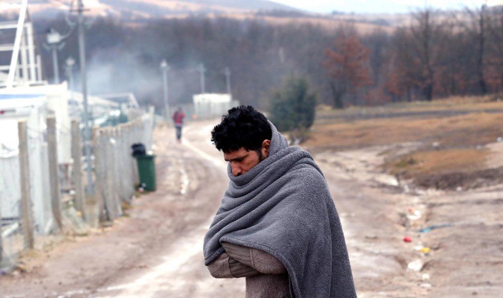 مهاجر يحاول تدفئة نفسه في مخيم ليبا في بيهاتش، البوسنة والهرسك