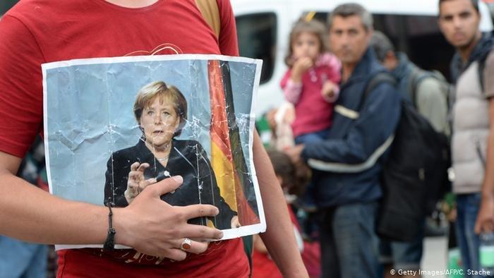 لاجئ في المجر يحمل صورة المستشارة ميركل
