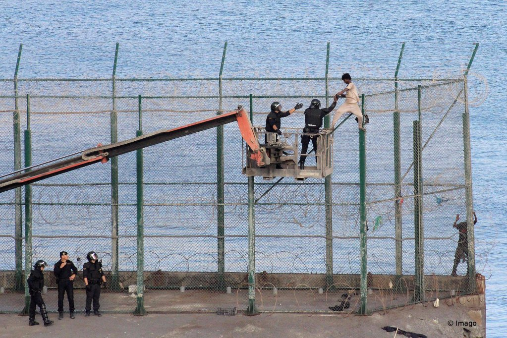 A migrant is detained by police on a crane as he remained on top of the border fence to jump onto Spanish soil in the Spanish enclave of Ceuta. Over 150 migrants managed to enter into Spain from Morocco in the mass breach | Credit: Imago/Reduan Dris Regragui