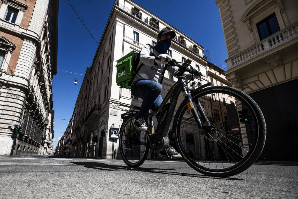 A Uber Eats rider passes on a deserted Via del Corso during the emergency blockade of the Coronavirus in Rome, Italy, 26 April 2020 | Photo: ANSA/ANGELO CARCONI