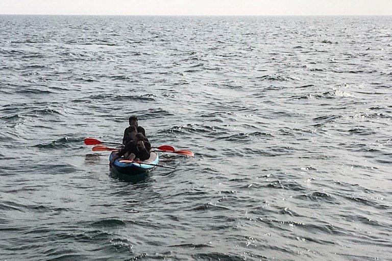 STR / AFP |Trois migrants tentant de traverser la Manche entre la France et la Grande-Bretagne dans un canoë gonflable au large des côtes françaises à Calais, le 4 août 2018.