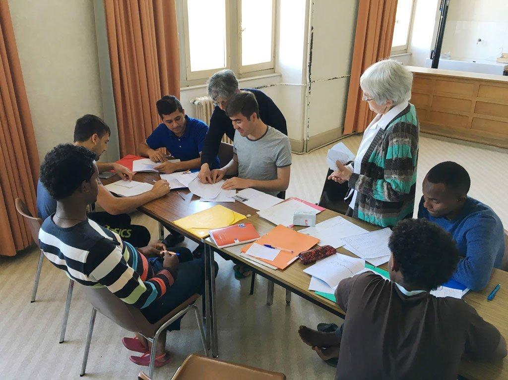 Ville d'Uzerche/uzerche.fr |Une douzaine de bénévoles se relaient chaque jour, comme ici avec Mesdames Armand et Chastre, et donnent plusieurs heures de cours de français aux migrants uzerchois (capture d'écran).