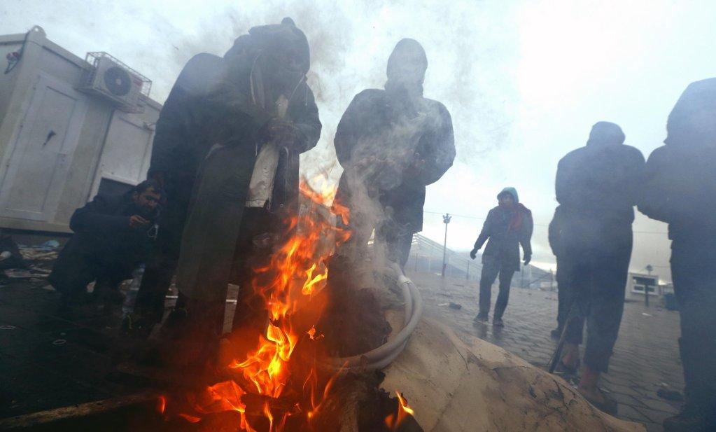 مهاجرون يشعلون الحطب طلباً للدفء في أحد أيام الشتاء داخل مخيم ليبا في بيهاتش بالبوسنة والهرسك. المصدر: إي بي إيه / فهيم دمير.