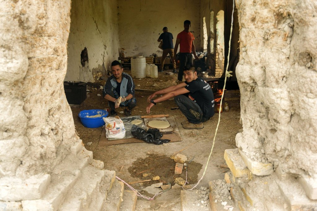 ANSA / مهاجرون يستعدون لإعداد الخبز في مبنى مهجور في ضواحي هورجو في شمال صربيا، بالقرب من الحدود مع المجر. المصدر: إي بي أيه/ إدفارد مولنار.
