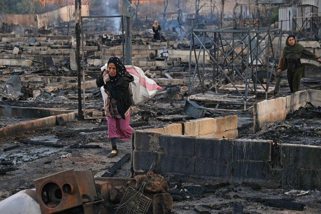 | لاجئون سوريون يأخذون بقايا متعلقاتهم من حريق مخيم المنية