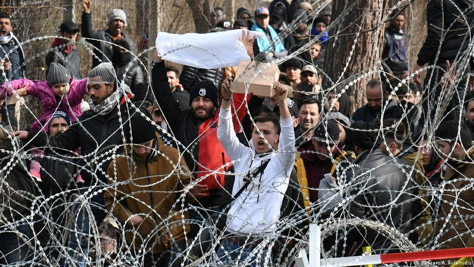 Groups of migrants on Turkey's Pazarkule border to Greece stand behind rolls of barbed wire | Photo: A.Avramidis/Reuters