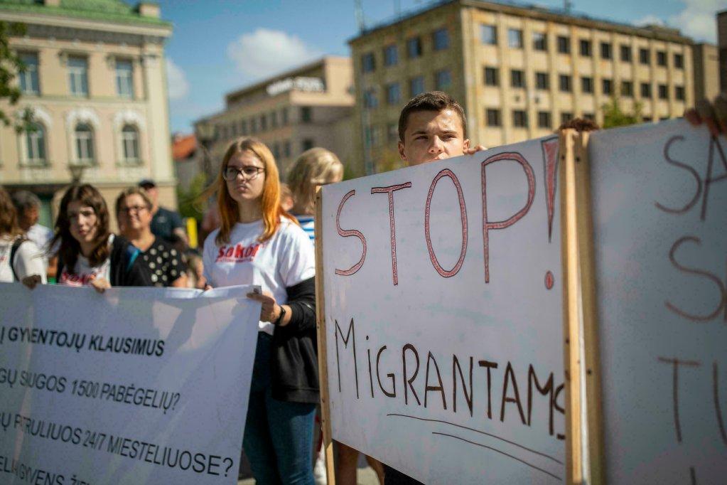 """Un manifestant tient un panneau sur lequel on peut lire """"Stop Migration"""" lors d'une manifestation anti-migrants devant le palais du gouvernement à Vilnius, en Lituanie, le 29 juillet 2021. Crédit : AP"""