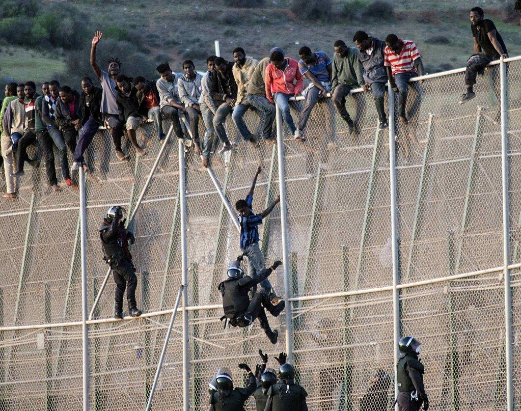 Des migrants franchissent la barrière entre Melilla et le Maroc. Crédit : Reuters (Archive)