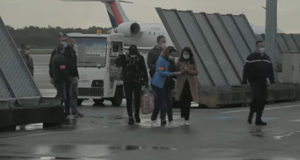 Ismail, au centre, est accompagné d'une quinzaine d'officiels et de policiers au moment de débarquer en France  | Source : Capture d'écran Channel 4 News