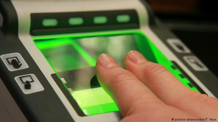 A person holds two fingers against an electronic fingerprint scanner