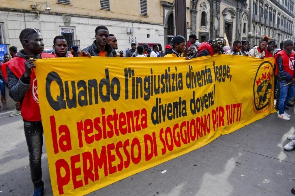 """ANSA / لافتة كتب عليها """"عندما يصبح الظلم قانونا تكون المقاومة واجبة.. وتصاريح الإقامة للجميع"""" في مظاهرة للمهاجرين في نابولي. المصدر: أنسا/ سيرو فوسكو."""