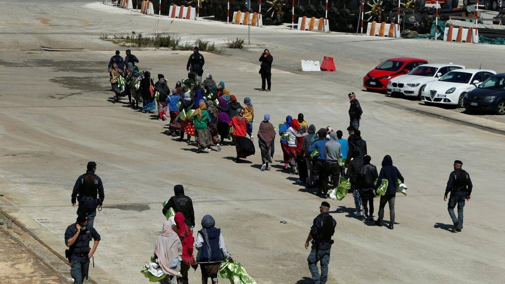 مهاجرون يسيرون تحت أعين رجال الشرطة  في صقلية / رويترز