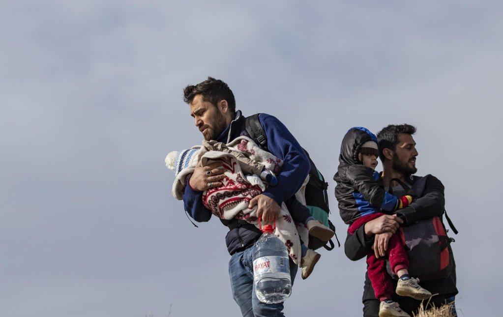 Migrant men holding children walk toward the Turkish-Greek border crossings from the city center of Edirne, Turkey   Photo: EPA/Erdem Sahin