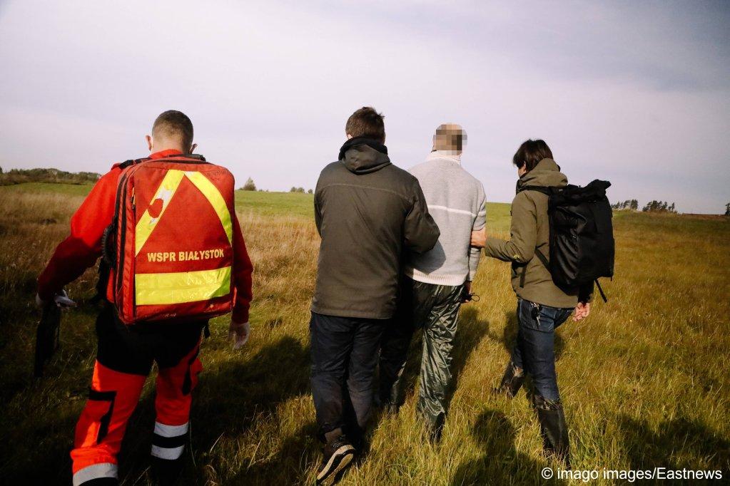 مسعفون  يساعدون طالب لجوء عراقي بعد إغماءه في غابة خارج المنطقة التي تشملها حالة الطوارئ في 3 أكتوبر 2021 في منطقة بودلاسي بشرق بولندا