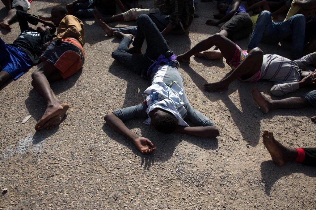 """ansa / مهاجرون أنقذتهم القوات الليبية ينتظرون في الميناء التجاري في طرابلس، قبل نقلهم إلى أحد مراكز الاحتجاز. المصدر: صورة أرشيف من """"إي بي إيه""""."""