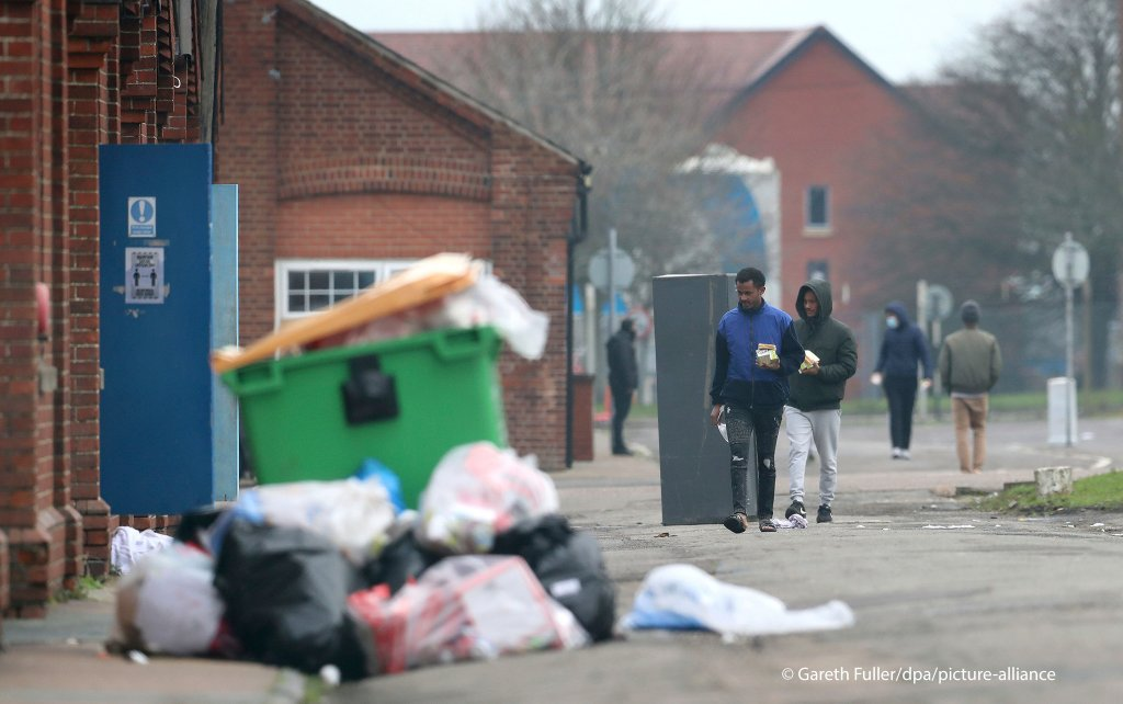 Migrants walk in the grounds of Napier Barracks in Folkestone, Kent, England following a fire at the site, Sunday, Jan. 31, 2021.| Photo: Gareth Fuller/PA via AP