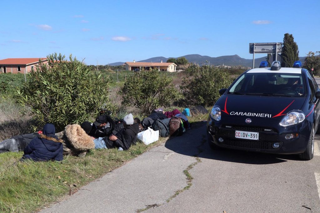 Carabinieri stop a group of migrants on the beach of Porto Pino on the southeast coast of Sardinia | Photo: ANSA/ FABIO MURRU