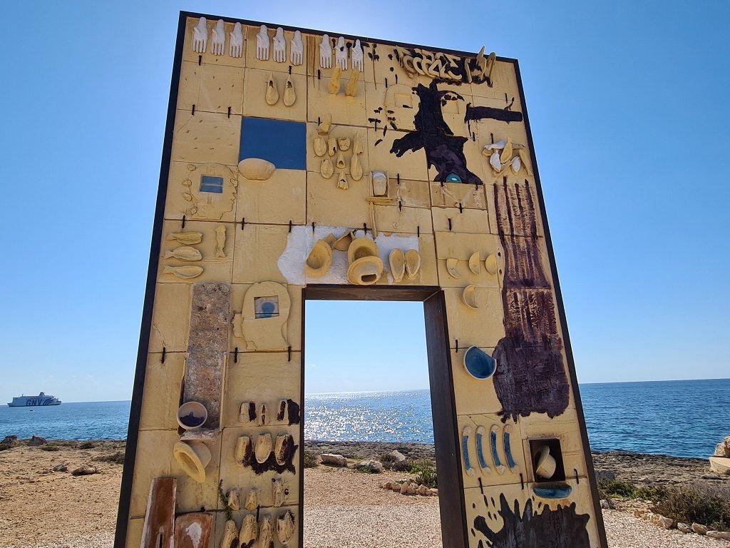 """""""بوابة أوروبا""""، عمل فني منصوب على السواحل الجنوبية للامبيدوزا، يجسد مدخلا للقارة الأوروبية يمر عبره المهاجرون الذين عبروا المتوسط بحثا عن الحياة الأفضل. شريف بيبي"""