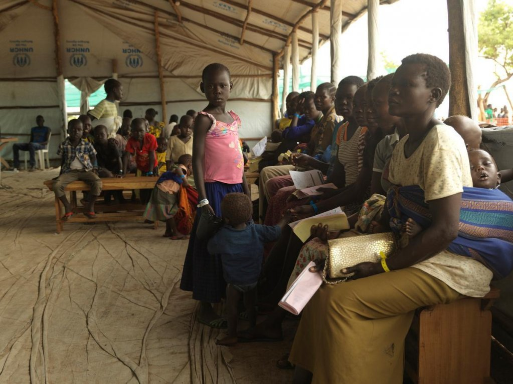 Photo: South Sudanese women and children wait to be registered at Imvepi settlement in northern Uganda. Credit: UNHCR/Peter Caton