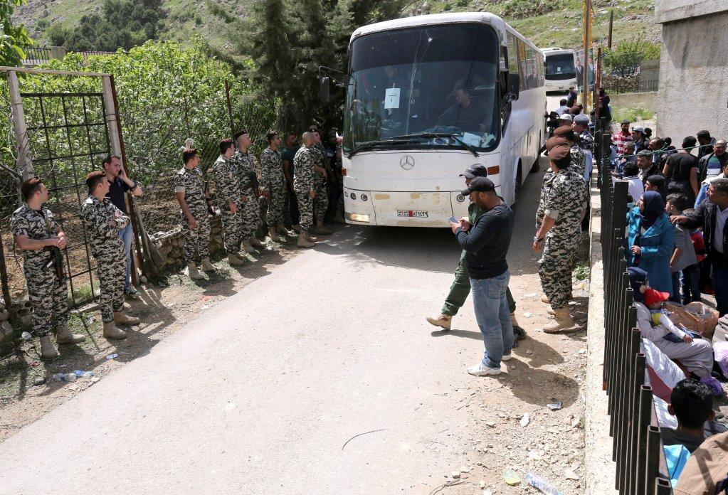 عنصر من جهاز الأمن العام اللبناني يحمل طفلا سوريا ويقود آخر باتجاه إحدى الحافلات المخصصة لنقل لاجئين سوريين من لبنان إلى سوريا، الأربعاء 18 نيسان/أبريل 2018. رويترز