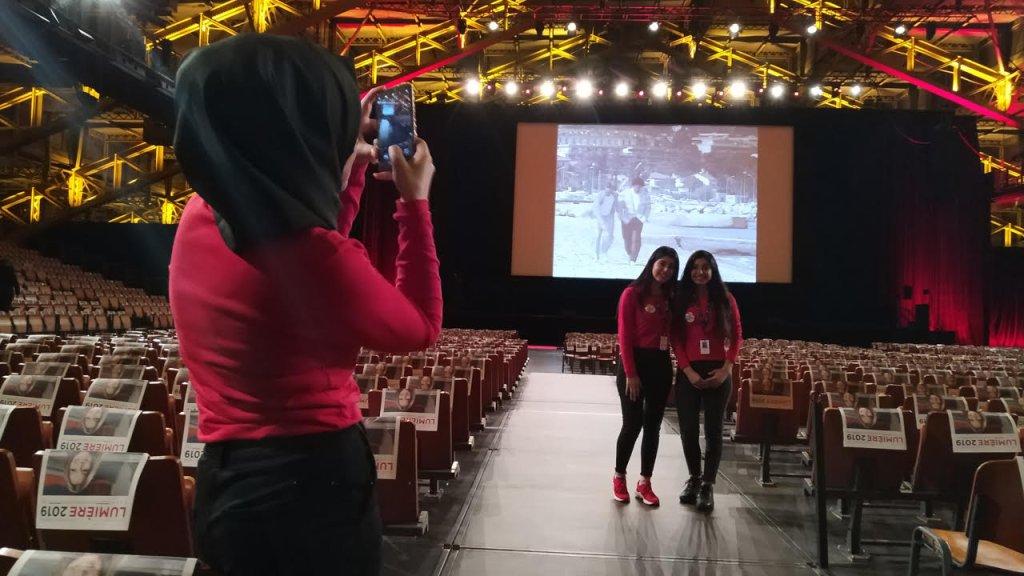 Fatmeh, à droite sur l'estrade, pose avec sa petite sœur dans la Halle Tony Garnier avant la projection d'Astérix et Obélix : Mission Cléopâtre. Crédit : InfoMigrants