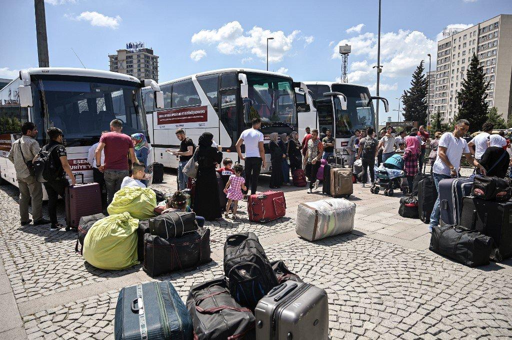 AFP Photos/Ozan KOSE |Des familles de réfugiés syriens attendent à Istanbul avant de monter dans des bus pour leur retour en Syrie (image d'illustration).