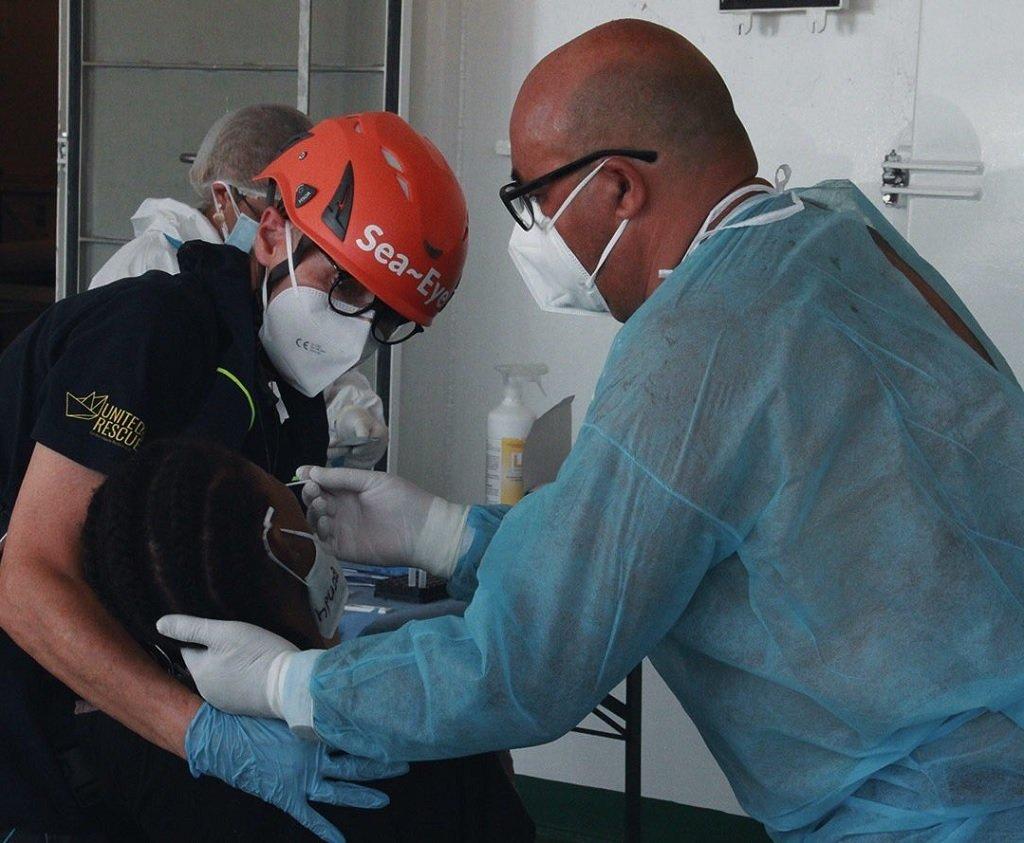 """أفراد من طاقم """"سي آي 4"""" يقدمون العناية الطبية لأحد المهاجرين قبيل إنزاله في ميناء أمبيدوكلي في صقلية، 5 أيلول\سبتمبر 2021. المصدر: منظمة """"سي آي"""" الألمانية"""