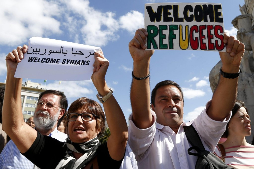 People holding up placards saying 'Welcome Refugees' as part of a demonstration in support of migrants in Lisbon, Portugal. Credit: EPA/ANTONIO COTRIM