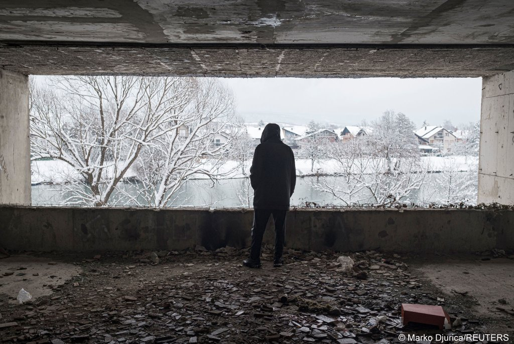 A migrant looks out of a window on January 11, 2021 as hundreds of them are taking shelter in abandoned buildings in the northwestern town of Bihac in Bosnia and Herzegovina | Photo: Marko Djurica/Reuters