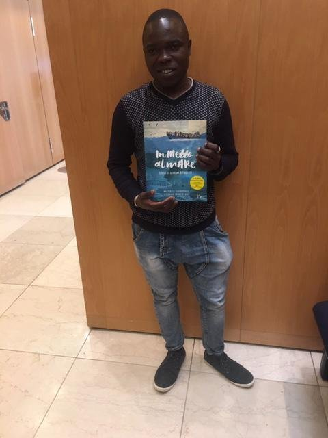 """Mohamed with the book  """"Stormy Seas"""" 