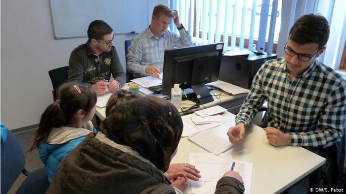 کارمندان اداره مهاجرت آلمان در حال ثبت درخواست پناهندگی یک پناهجو