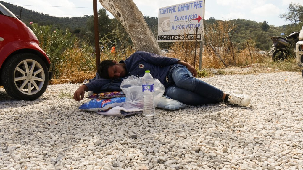 مهاجری که در جزیره لیسبوس روی زمین خوابیده است. عکس از سلیم عاصم/ مهاجر نیوز