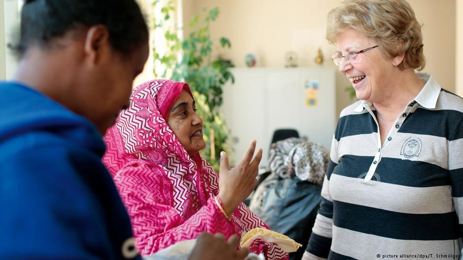 A volunteer gives advice to refugees in Aachen, Germany