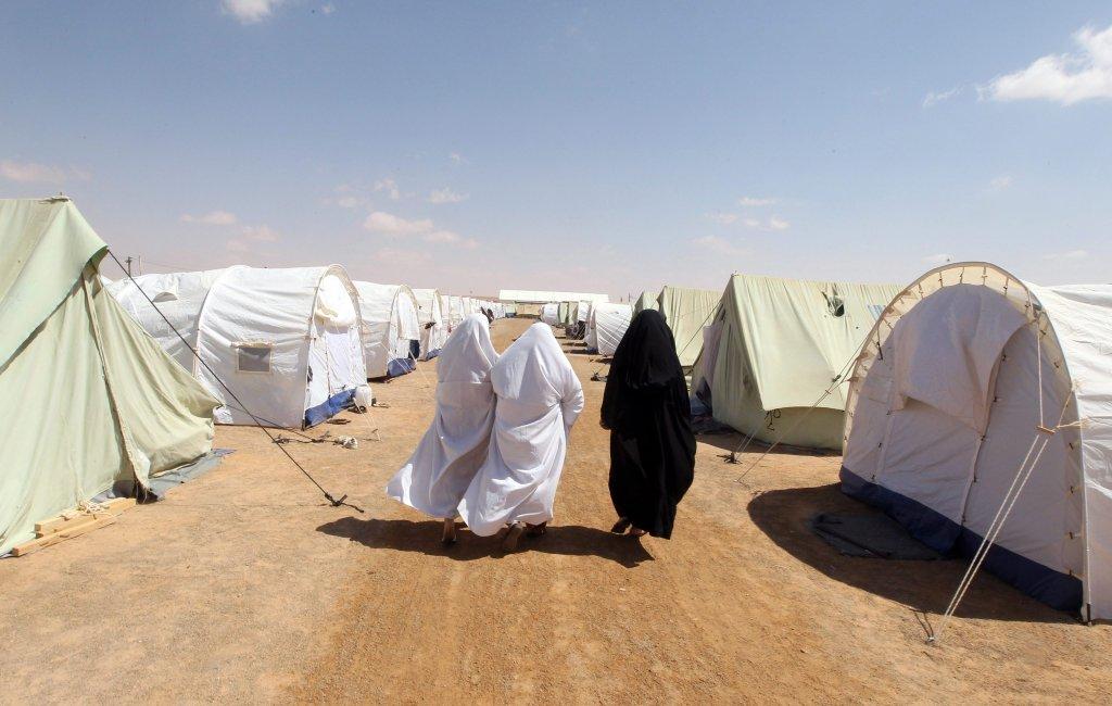 لاجئون ليبيون، ممن فروا من العنف في ليبيا، يمشون داخل مخيم تم افتتاحه مؤخرا لإيواء الأسر الليبية في منطقة الرمادة التونسية، على بعد 25 كيلو مترا جنوب الحدود التونسية الليبية. المصدر: إي بي إيه/ محمد ميسارا.