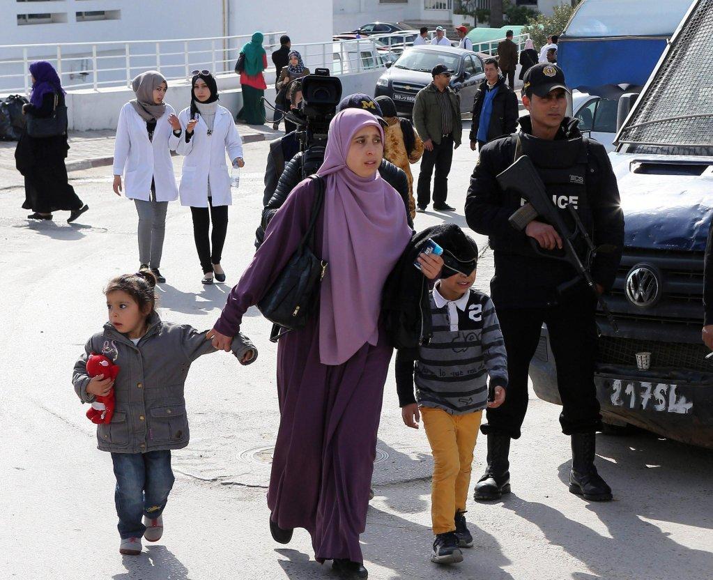 ansa / أم وطفلاها يسيرون إلى جانب رجال الشرطة في تونس. المصدر: إي بي أيه