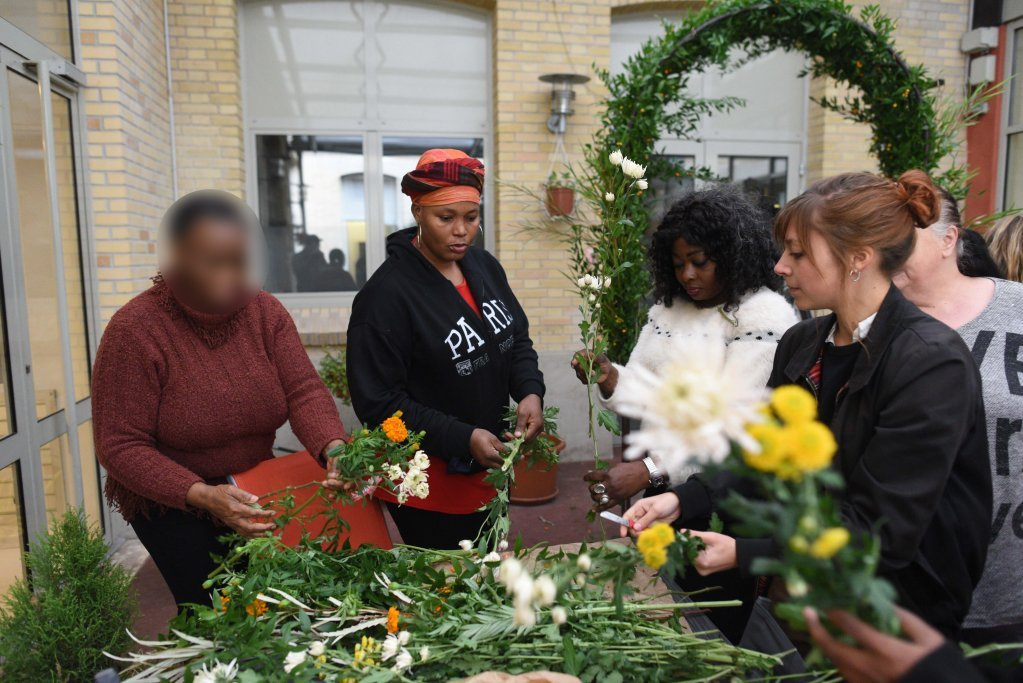 Tarya, an undocumented migrant from Cameroon, Ami, an asylum seeker from Ivory Coast, and Matoumona, a, asylum seeker from DR Congo take part in the weekly workshop run by Du Pain & des Roses. Lucile (right) is one of the florists teaching them the art of floral decoration | Photo: Mehdi Chebil