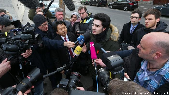 Anas M., who became the victim of an anti-refugee smear campaign on Facebook after taking a selfie with Chancellor Angela Merkel, speaks to reporters outside a courthouse in Bavaria