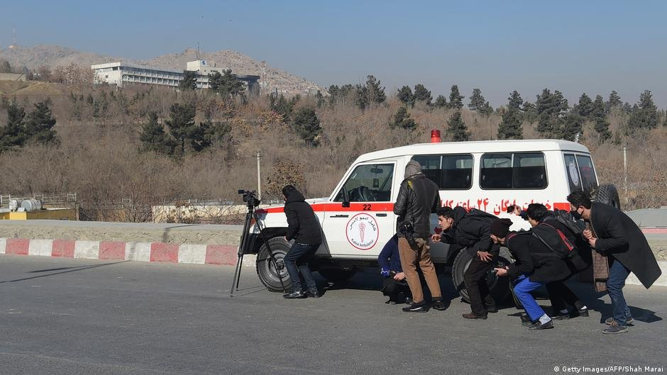 Afghan journalists take cover near a hotel in Kabul during a fight between gunmen and Afghan security forces in 2018 | Photo: Getty Images (via DW)
