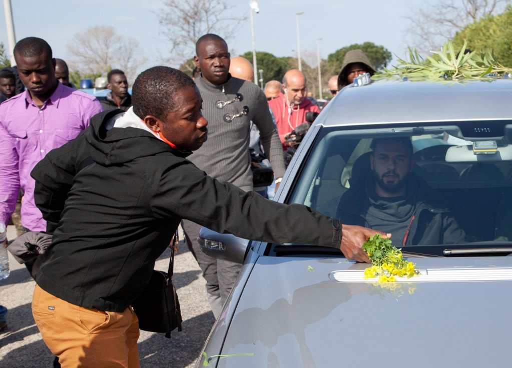 A migrant worker leaves flowers on the car taking away the coffin with the body Sylla Noumo, who died in the fire. Photo: ANSA