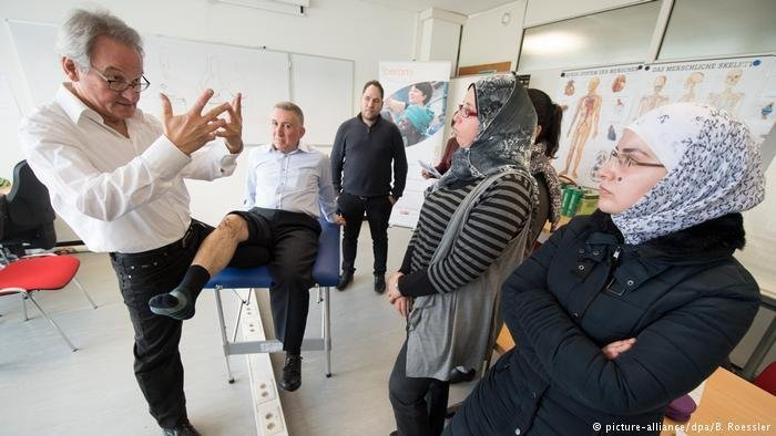 A German doctor explains things to a group of refugee doctors | Photo: picture-alliance / dpa / B. Roessler