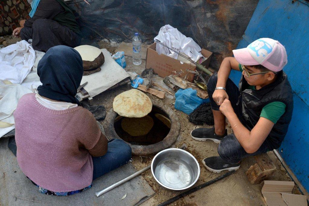 """ANSA / مهاجرون يعدون خبز """"نان"""" الهندي التقليدي، بالقرب من مخيم موريا في جزيرة ليسبوس اليونانية. المصدر: إي بي إيه / ستراتيس بالاسكاس."""