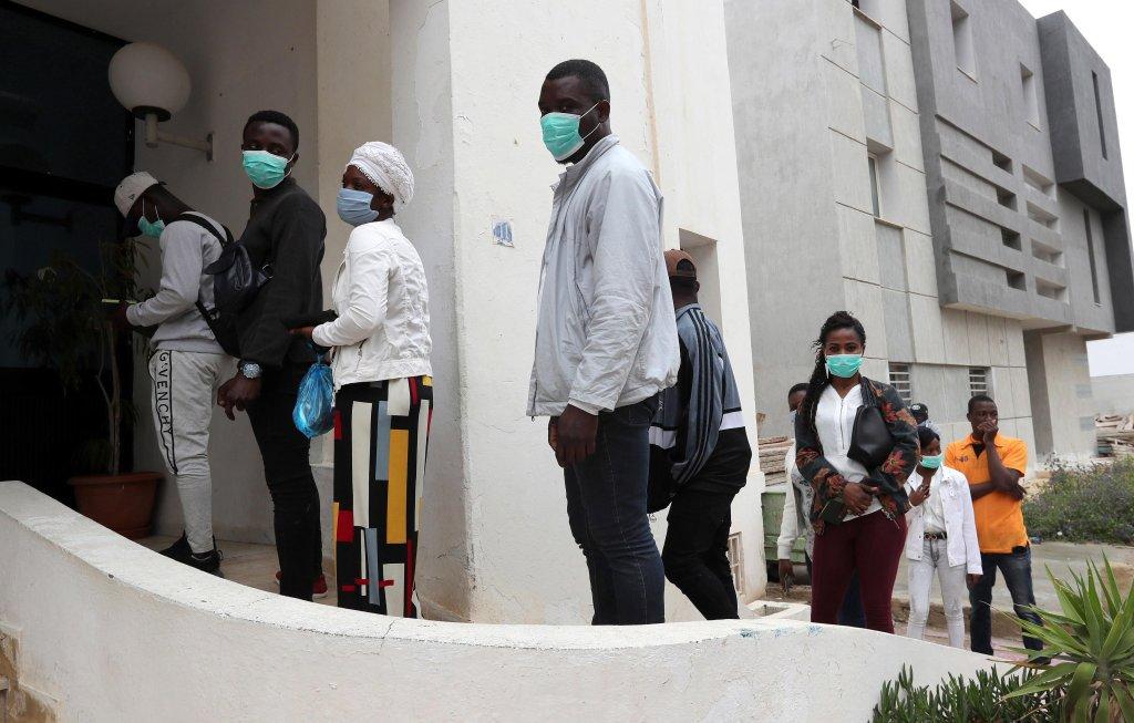 Des immigrés africains font la queue pour recevoir des cartons de secours distribuées par la mairie de Raoued à Tunis, Tunisie, le 22 avril 2020. Crédit : EPA