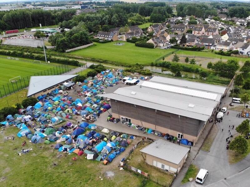 کمپ متشکل از خیمههای مهاجران در اطراف سالن ورزشی گراندسنت. عکس از سولیداریتی باردرز