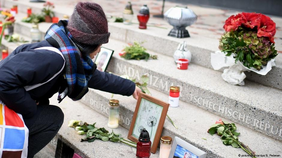 A woman placing a flower at Breitscheidplatz memorial | Photo: Picture.alliance/dpa/B.Pedersen