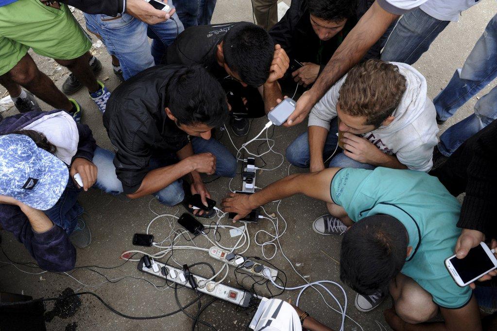 عکس تزئینی: گروهی از مهاجران در حال چارج کردن تیلفونهای موبایل خود در مرز مقدونیا با یونان. عکس از رویترز/ الکساندر آرامیدیس