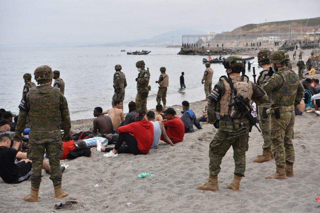 © أ ف ب |المهاجرون الذين وصلوا سباحة إلى سبتة الإسبانية يستريحون بينما يقف الجنود الإسبان في الحراسة 18 مايو 2021 في سبتة.