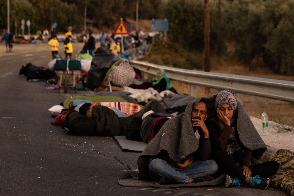 Un couple de migrants, sans abri suite à l'incendie du camp de Moria, se retrouvent assis par terre sur une route, jeudi 10 septembre. Crédit : Reuters