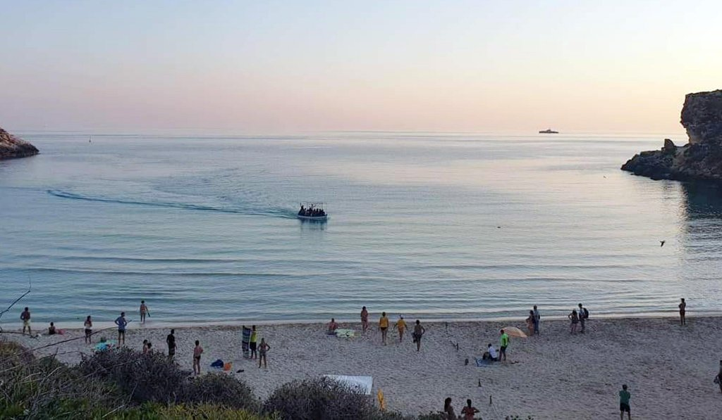 A boat with 21 Tunisians aboard arrives amid tourists on Lampedusa's Conigli Island beach, September 14, 2019 | Photo: ANSA/Concetta Rizzo