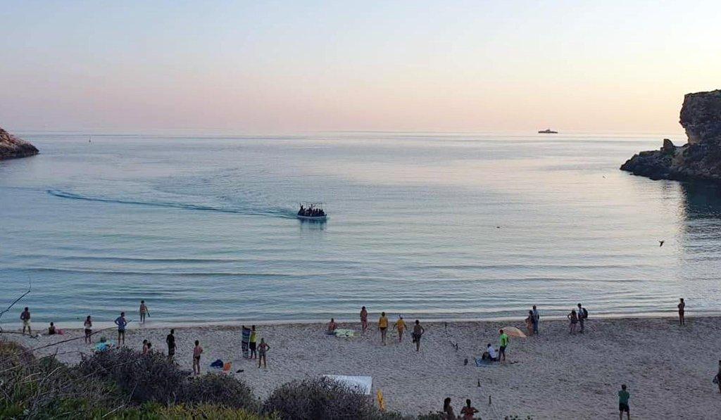 Un bateau avec 21 Tunisiens à bord arrive parmi les touristes sur la plage de l'île de Conigli à Lampedusa, le 14 septembre 2019. Crédit : ANSA