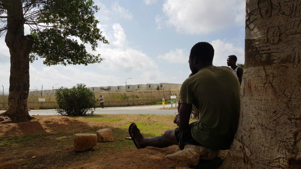 مهاجر ينظر إلى مركز هال فار في مالطا. ودفع الاكتظاظ في هذه المخيمات المهاجرين للحياة دون مأوى في الشارع. أرشيف. المصدر/ مهاجر نيوز